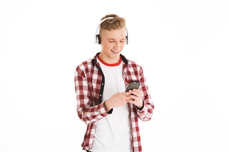 Aantrekkelijke man in casual t-shirt 17y dragen bretels luisteren naar favoriete melodie via draadloze hoofdtelefoons en met behulp van moderne gadget geïsoleerd op witte achtergrond