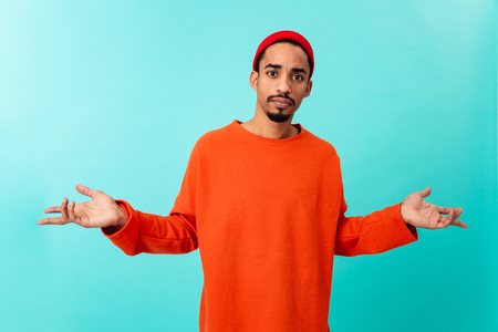 Portrait of a confused young afro american man in hat gesturing with hands isolated over blue background