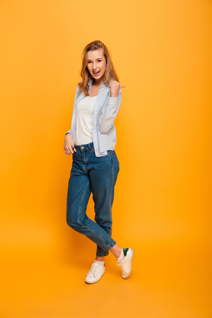 Full length photo of pleased woman wearing casual jeans smiling and pointing finger backward on copyspace1 isolated over yellow background