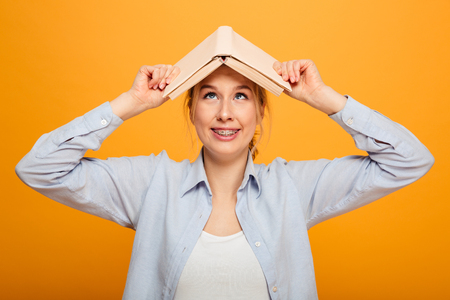 Image of funny young lady student standing isolated over yellow background holding book.