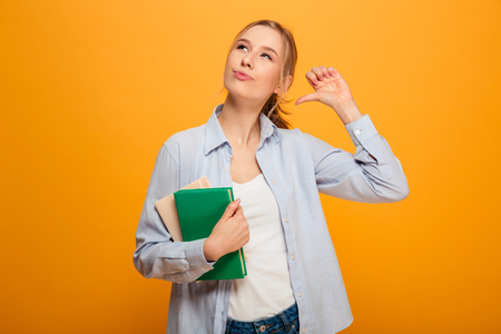 Photo of serious young woman student standing isolated over yellow background. Looking aside pointing holding books.