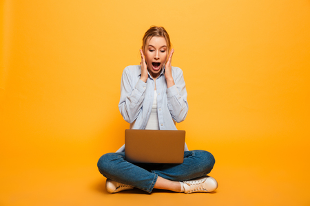 Image of shocked young lady student sitting isolated over yellow background. Looking aside using laptop computer.