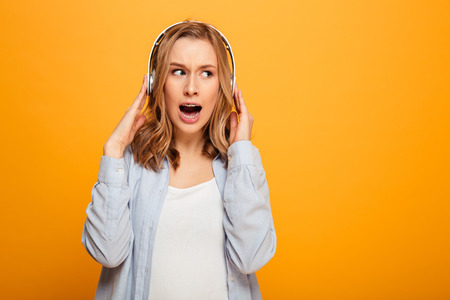 Picture of brunette woman wearing braces emotionally react on music while listening song or tune using wireless headphones isolated over yellow background Stock Photo