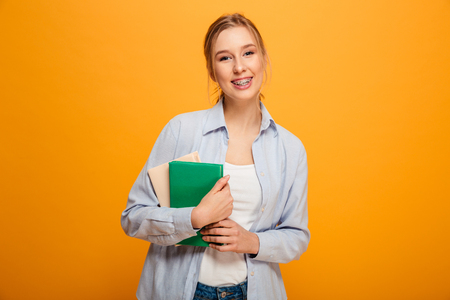 Photo of cheerful young lady student standing isolated over yellow background. Looking camera holding books. Stok Fotoğraf