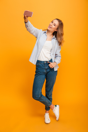 Studio portrait of beautiful woman smiling and taking selfie photographing herself isolated over yellow background
