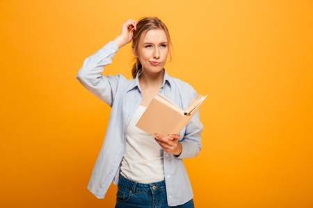 Image of serious thinking young lady student standing isolated over yellow background reading book.