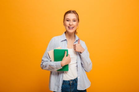 Photo of happy young lady student standing isolated over yellow background. Looking camera with thumbs up holding books. Stok Fotoğraf