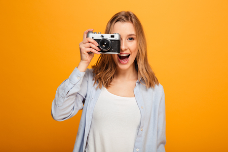 Portrait of a happy young girl with braces taking photo with camera isolated over yellow background