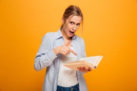 Image of displeased young lady student standing isolated over yellow background reading book. Looking camera. 스톡 콘텐츠