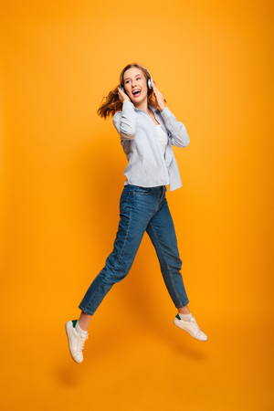Image of happy young woman jumping listening music isolated over yellow background.