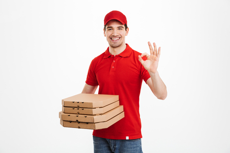 Deliveryman 25y in red t-shirt and cap holding stack of pizza boxes and showing ok sign isolated over white background