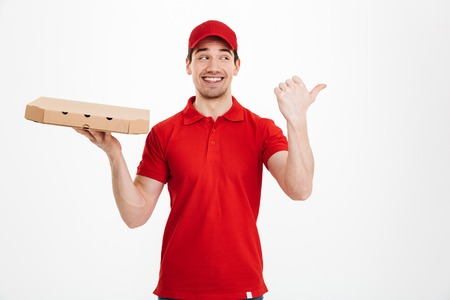 Image of a smiling young delivery man in red cap standing pointing isolated over white background. Looking aside holding pizza.