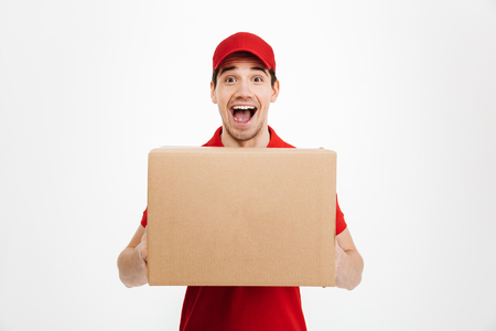 Image of a young shocked excited delivery man in red cap standing with parcel post box isolated over white background. Looking camera.
