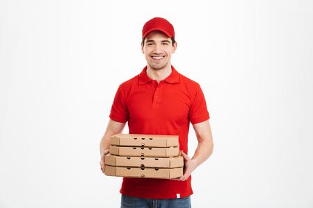 白い背景に隔離されたピザボックスの赤いTシャツとキャップ保持スタックの笑顔の配達員の画像