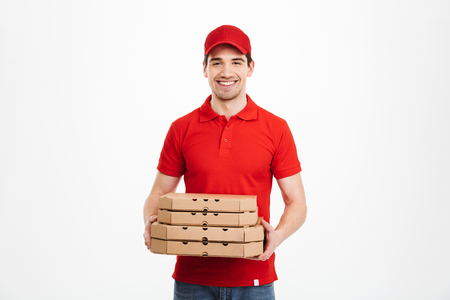 Image of smiling deliveryman in red t-shirt and cap holding stack of pizza boxes isolated over white background