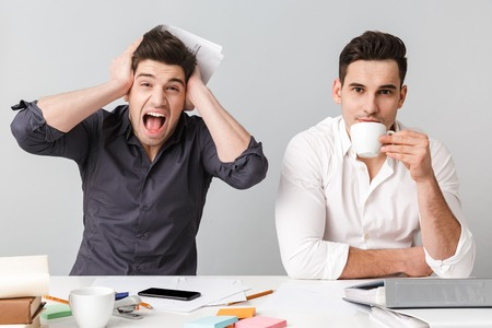 Image of screaming confused young business man near his colleague drinking coffee sitting isolated over grey wall at the table.