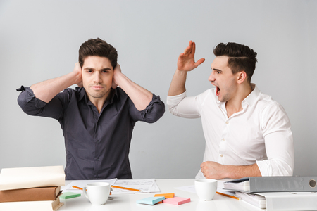 Image of displeased young business man covering ears because of dont want to hear his colleague sitting isolated over grey wall at the table.