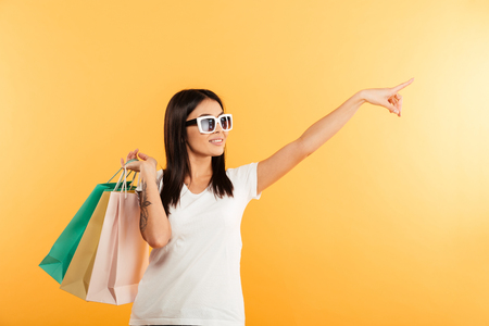 Portrait of a happy young asian girl holding shopping bags and pointing away at copy space isolated over yellow background Imagens