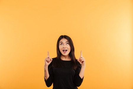 Image of excited young happy woman standing isolated over yellow background looking aside pointing. Stock fotó