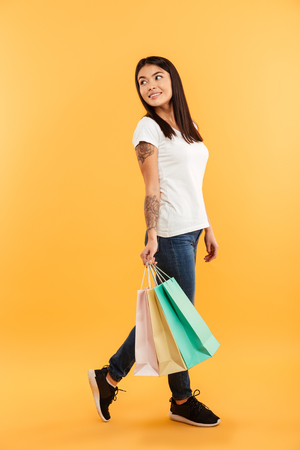Full length portrait of a smiling young asian girl walking with shopping bags isolated over yellow background