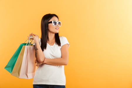 Portrait of a smiling young asian girl holding shopping bags and looking away at copy space isolated over yellow background