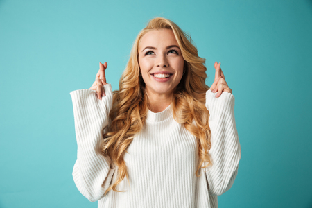 Portrait of an excited young blonde woman in sweater holding fingers crossed for good luck isolated over blue background Archivio Fotografico - 99827106