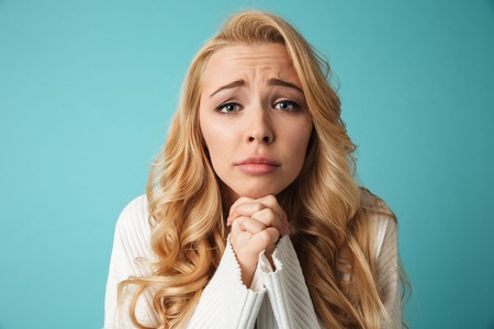Close up portrait of a pretty young blonde girl looking at camera and begging isolated over blue background Foto de archivo