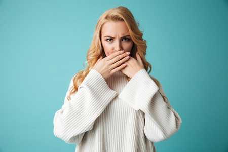 Portrait of an angry young blonde woman in sweater covering mouth with hands isolated over blue background