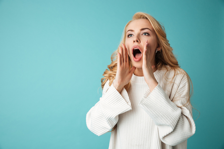 Portrait of a pretty young blonde girl calling for someone isolated over blue background