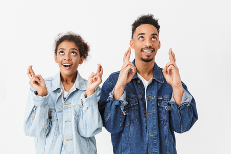 Smiling african couple in denim shirts praying together with crossed fingers while looking up over grey background Stock Photo
