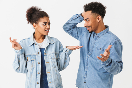Pretty african couple in denim shirts quarrels between themselves over grey background