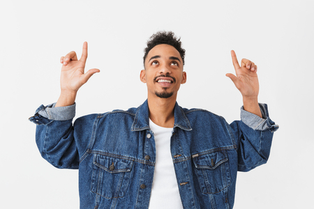 Smiling african man in denim jacket pointing with forefingers and looking up over grey background Banco de Imagens