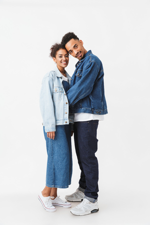 Full length image of Smiling african couple in denim shirts posing together and looking at the camera over grey background Stock Photo