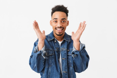 Surprised happy african man in denim jacket looking at the camera over grey background