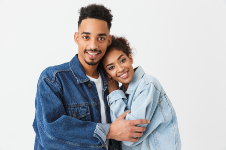 Cheerful african couple in denim shirts hugging together while looking at the camera over grey background Banque d'images