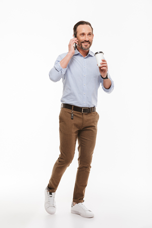 Full length portrait of a happy mature man dressed in shirt holding takeaway coffee cup while walking and talking on mobile phone isolated over white background