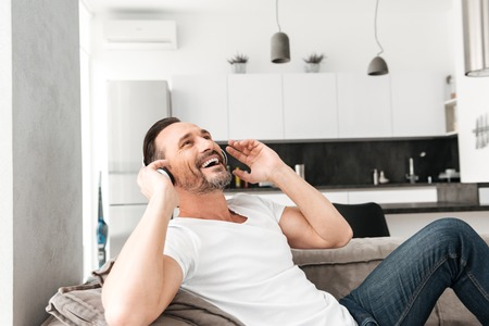 Delightened mature man listening to music with headphones while resting on a sofa at home