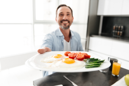Delightened mature man passing a plate while having tasty breakfast at the kitchen table