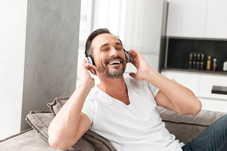 Smiling mature man listening to music with headphones while resting on a sofa at home