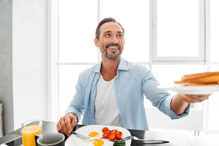 Happy mature man passing a plate while having tasty breakfast at the kitchen table Stock fotó