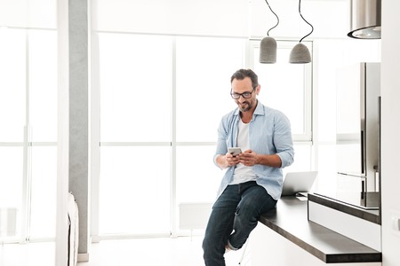 Smiling mature man using mobile phone while leaning on a kitchen table at home Stock Photo