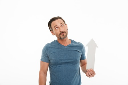 Portrait of a smiling mature man dressed in t-shirt pointing up with an arrow isolated over white background Stock Photo