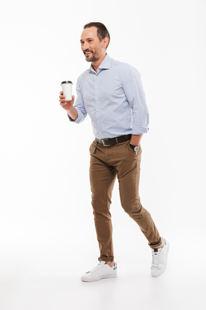 Full length portrait of a happy mature man dressed in shirt holding takeaway coffee cup while walking isolated over white background Stock Photo