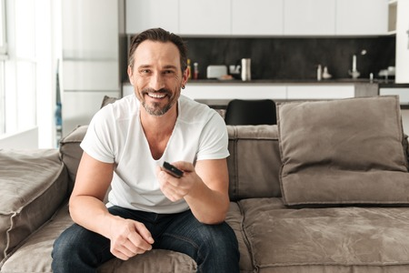 Smiling mature man sitting on a sofa with TV remote control at home Stock Photo