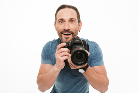 Portrait of an excited mature man dressed in t-shirt holding photo camera isolated over white background Stock Photo