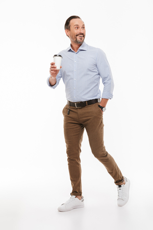 Full length portrait of a joyful mature man dressed in shirt holding takeaway coffee cup while walking isolated over white background