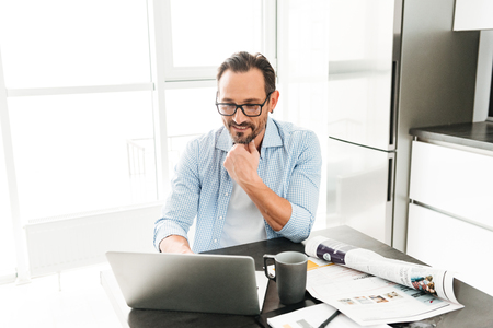 Handsome mature man using laptop computer while sitting at the table at home