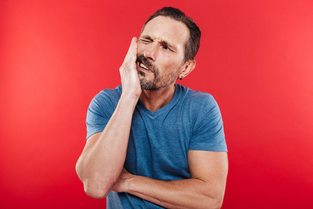 Portrait of adult bearded man suffering from toothache and touching jawbone with pain on face isolated over red background Stockfoto