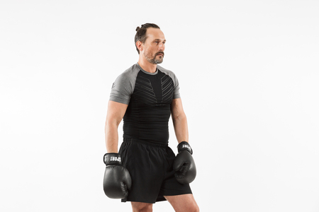 Portrait of a concentrated mature sportsman doing boxing isolated over white background