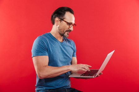 Portrait of an adult happy emotional positive man in colorful sunglasses standing isolated over red background looking aside using laptop computer.